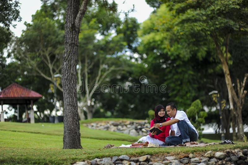 Campus life, student`s love. Beautiful couple learning together in the park. Education, love and tenderness, dating, romanc. E in Malaysia stock photos