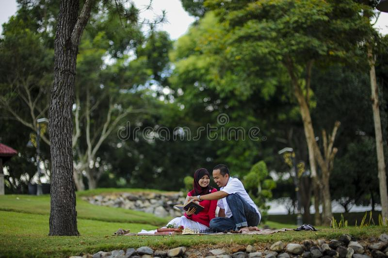 Campus life, student`s love. Beautiful couple learning together in the park. Education, love and tenderness, dating, romanc. E in Malaysia stock image