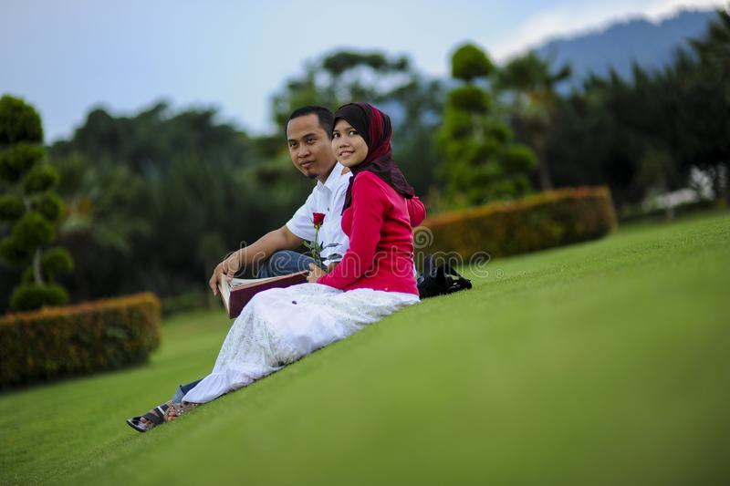 Campus life, student`s love. Beautiful couple learning together in the park. Education, love and tenderness, dating, romanc. E in Malaysia stock photography