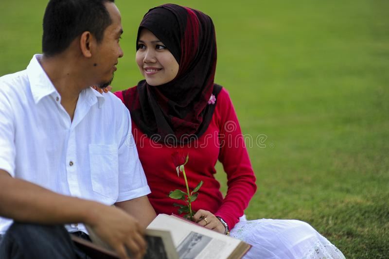 Campus life, student`s love. Beautiful couple learning together in the park. Education, love and tenderness, dating, romanc. E in Malaysia stock photo