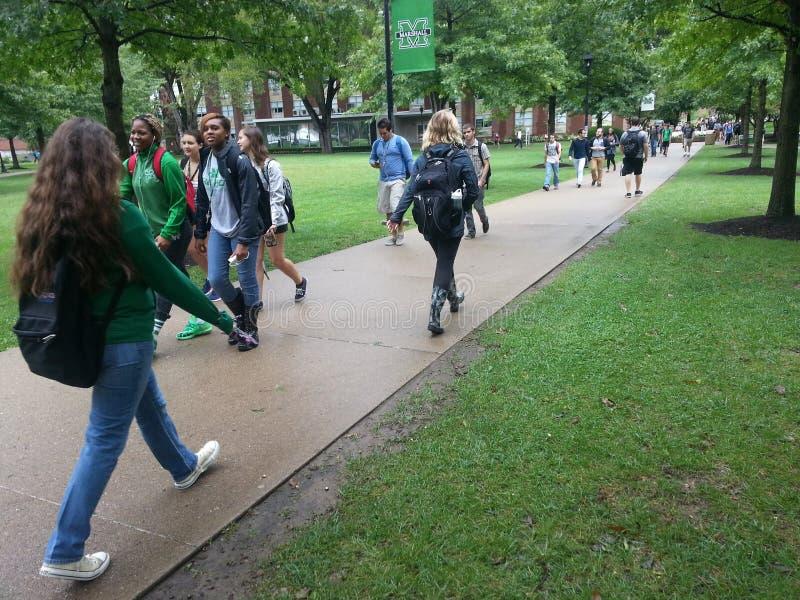 Campus universitario: Studenti che camminano fra la classe immagini stock