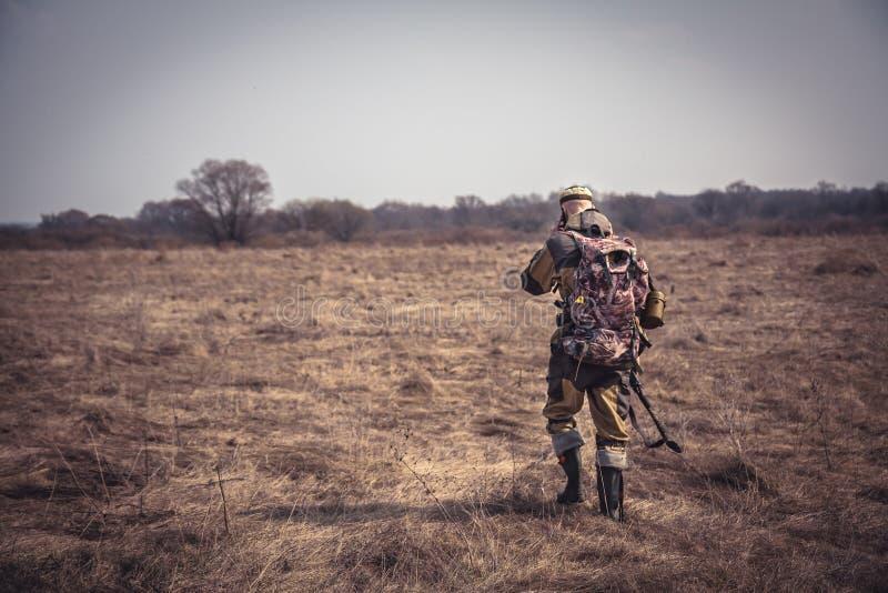 Camuflagem do homem do caçador com a espingarda e a trouxa que atravessam o campo rural durante a caça fotos de stock