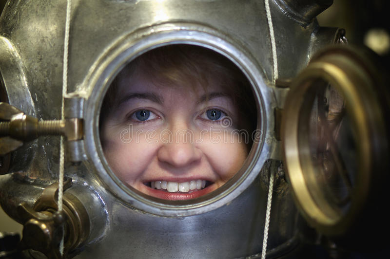 In The Can. Bright smiling face of woman wearing a vintage Mark V diving helmet. Paul Harling and Dan Tremblay of The Dive Locker, a diving museum in Gloucester stock images