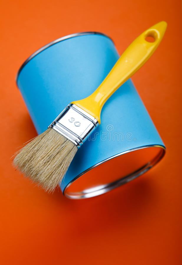 Can of blue paint and paintbrush on orange background.  royalty free stock photo