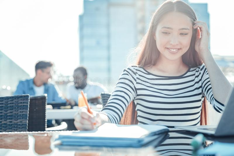 Positive delighted brunette female making notes stock photos