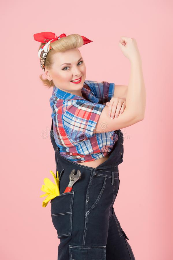 We Can Do It concept with blonde curls girl on pink background. Blonde Cute Girl repairer with hand up. stock image