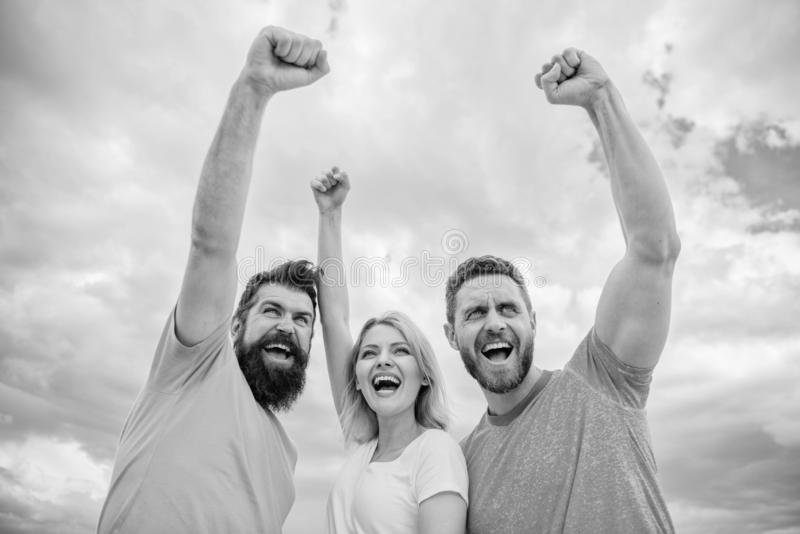 We can do it. Woman and men look successful celebrate victory sky background. Threesome stand happy with raised fists. Behaviors of winner team. Celebrate royalty free stock photo