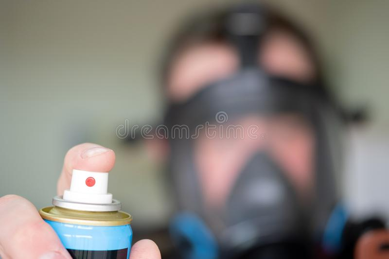 A can of gas in the foreground in the hand of a man the background of a man in a black gas mask blurred out of focus. Aerosol container with gas for the royalty free stock image
