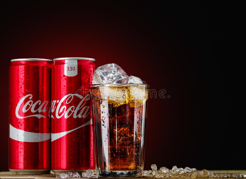 Can and glass of Coca-Cola with ice on wooden background. MINSK, BELARUS-OCTOBER 18, 2016: Can and glass of Coca-Cola with ice on wooden background. Coca-Cola stock photography