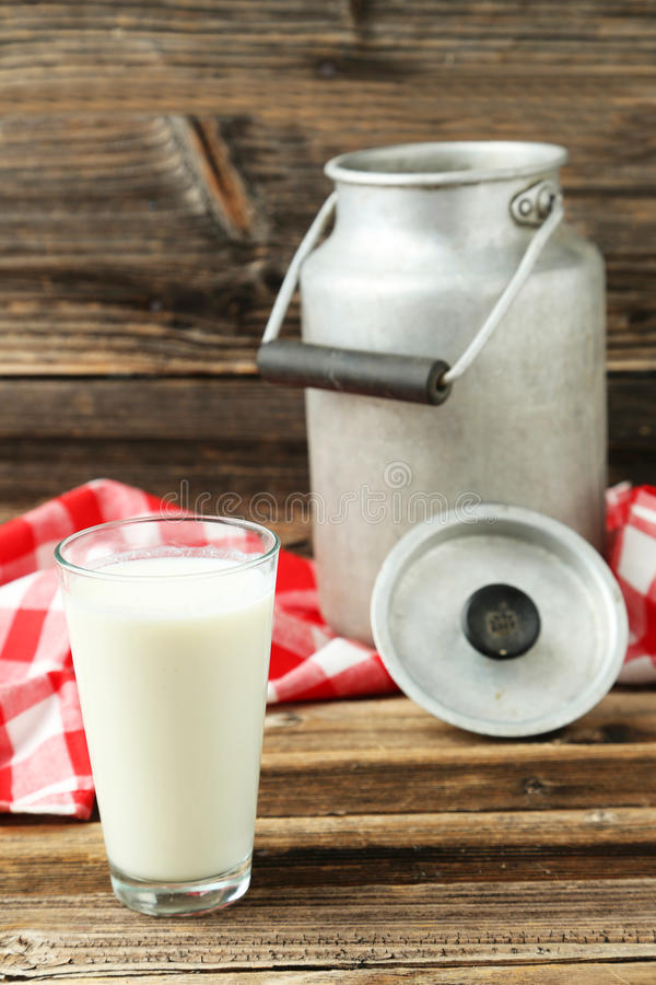 Can and glass of milk. On brown wooden background stock images
