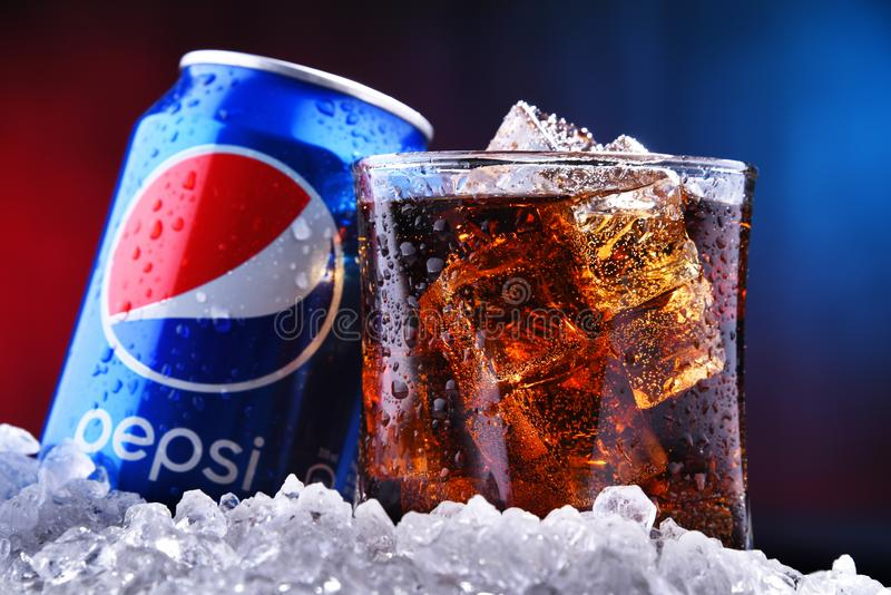 A can and a glass of Pepsi. POZNAN, POL - AUG 13, 2019: A can and a glass of Pepsi, a carbonated soft drink produced and manufactured by PepsiCo. The beverage royalty free stock photo