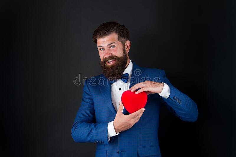 Can I help you. World heart day. brutal bearded hipster in formal suit. businessman in bow tie. Health care. Valentines royalty free stock image