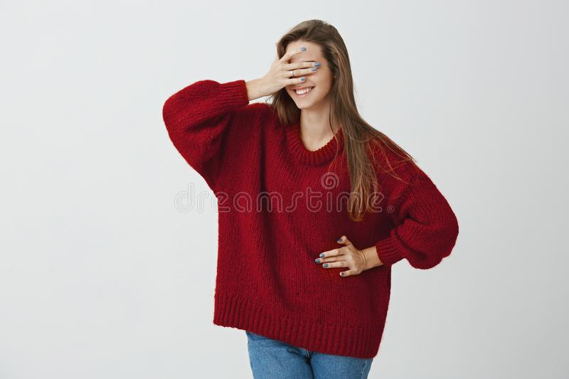 Can I look now. Curious and excited attractive woman in trendy loose red sweater covering eyes with hand and standing stock images