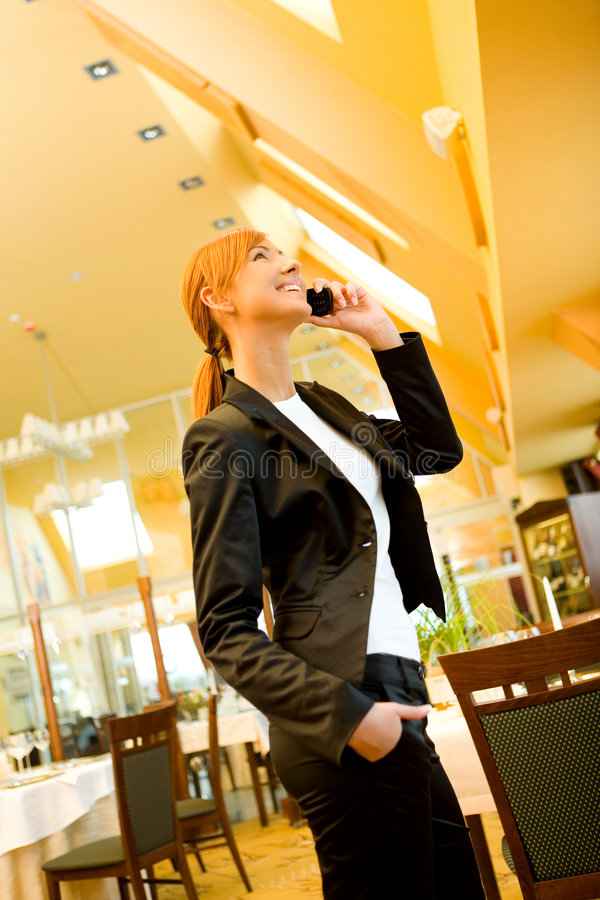 Can we meet in restaurant?. Red-haired young woman standing with hand in pocket and talking by cellphone. She's in restaurant stock photo