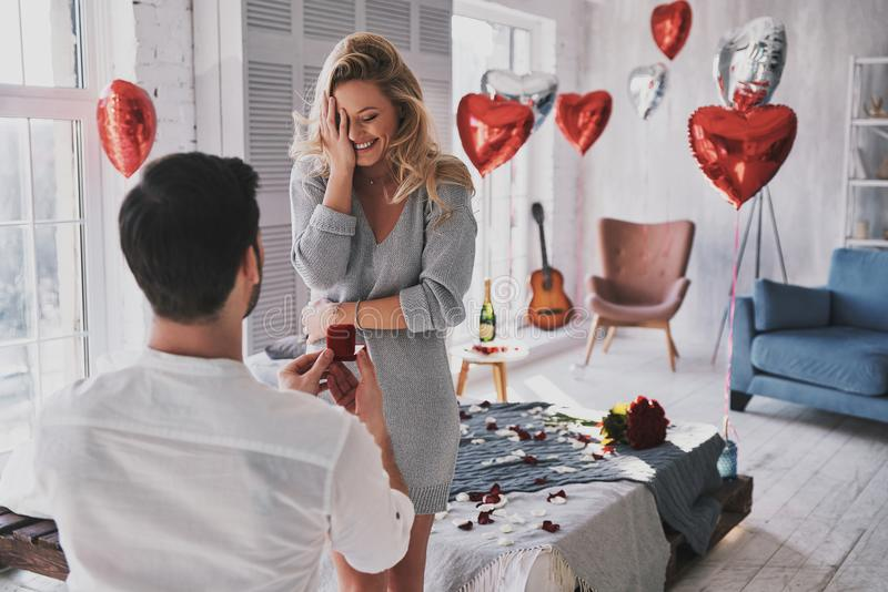 Can not believe this is happening! Surprised young woman covering face with hand and smiling while her boyfriend proposing her in. Can not believe this is royalty free stock photography