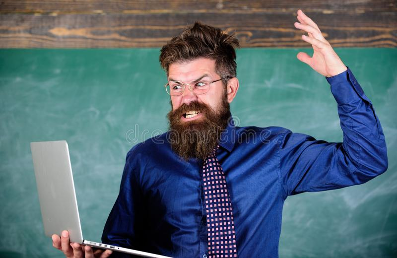 Can not get used to modern technology. Teacher bearded man with modern laptop chalkboard background. Hipster teacher. Aggressive with laptop goes mad about royalty free stock images