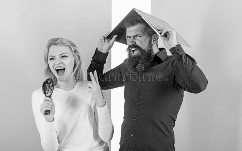 Can not stop song in her head. Lady sing using hair brush as microphone while man annoyed hiding under laptop. Better royalty free stock image