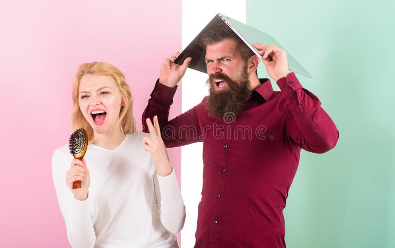 Can not stop song in her head. Lady sing using hair brush as microphone while man annoyed hiding under laptop. Better stock photos