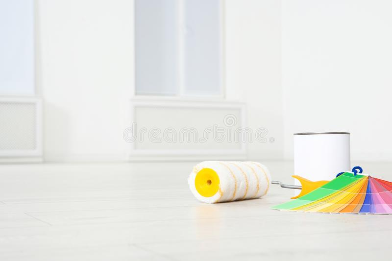 Can of paint, roller brush and color palette on wooden floor indoors. royalty free stock images
