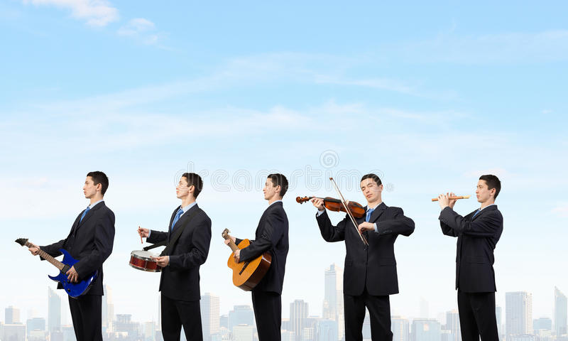 He can play all instruments. Man orchestra in suit playing different music instruments stock images