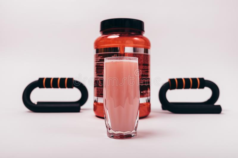 Can of protein and ready-made sports drink in glass. Next to the push-up devices. Muscle building kit stock images