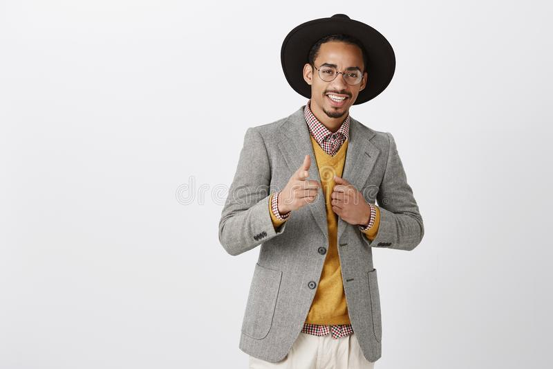 He can rely on you. Portrait of satisfied confident african-american guy in black hat and stylish jacket, showing gun stock image
