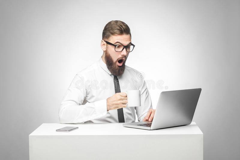 Can`t believe! Portrait of emotional shocked young businessman in white shirt and black tie are sitting in office, reading news stock photography