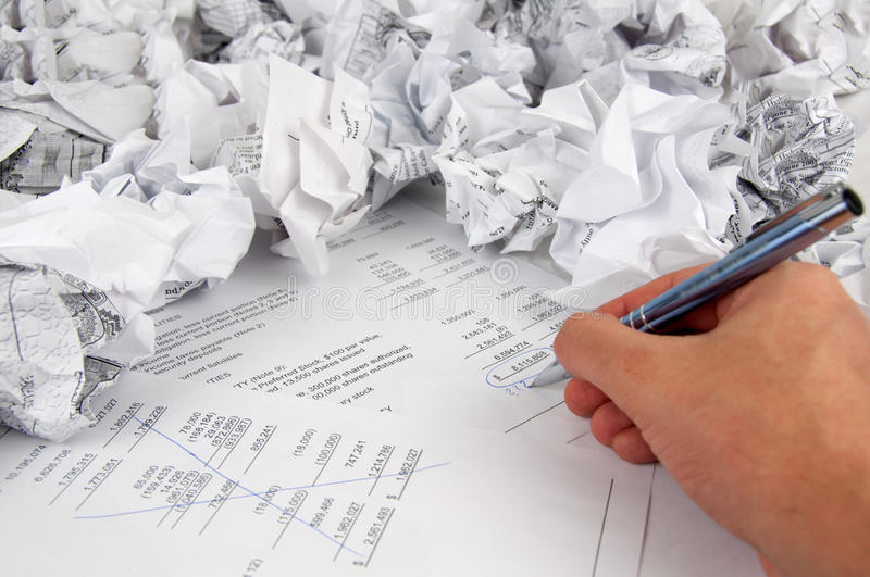 Can't make it. A photo shows a man's hand with pen and papers trying to make his own audit but it's not working The photo was shut in studio lights royalty free stock photo