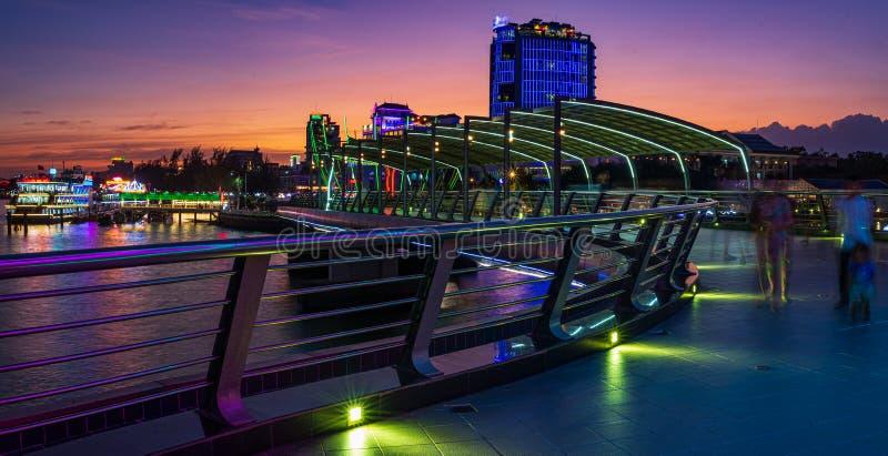 Can Tho city lights at dusk skyline pedestrian bridge on river, blurred motion people walking on waterfront promenade, Mekong. Delta region, Vietnam stock image