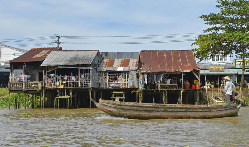 Buildings on Can Tho Waterway. Can Tho, Vietnam - December 31st 2017. A man on an old wooden boat goes past a row of small houses which look out onto a waterway stock photos