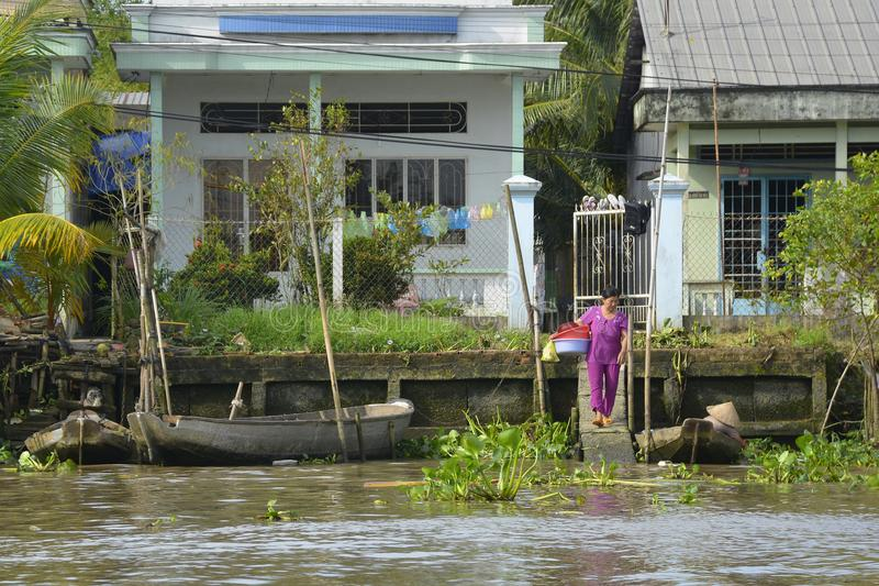 Buildings on Can Tho Waterway. Can Tho; Vietnam - December 31st 2017. A woman walks to the river to wash some dishes in plastic tubs at the back of her house royalty free stock photography