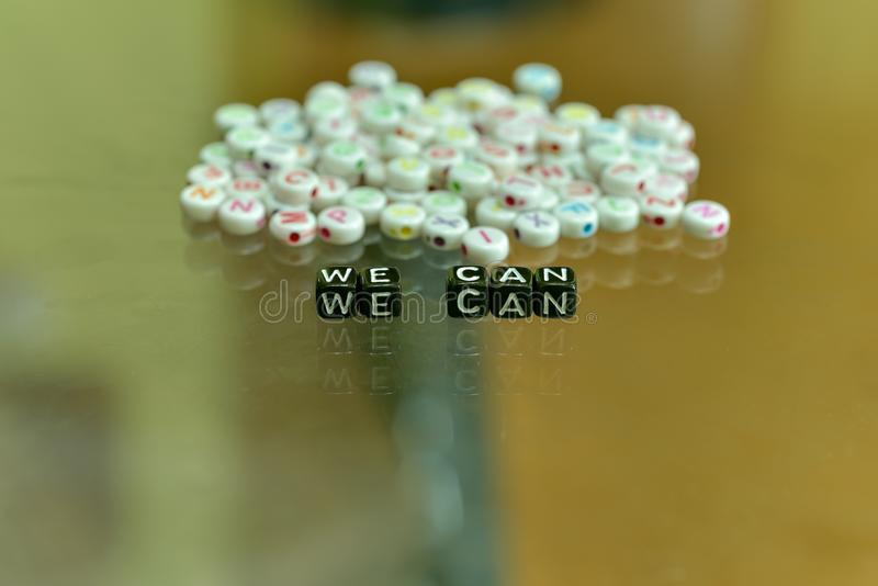 WE CAN  written with Acrylic Black cube with white Alphabet Beads on the Glass Background.  stock image