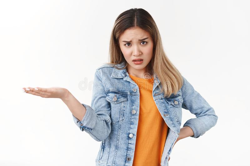 Can you explain this me. Angry intense displeased young bothered asian blond girl frowning frustrated hold confusing. Product hand look under forehead stock photos