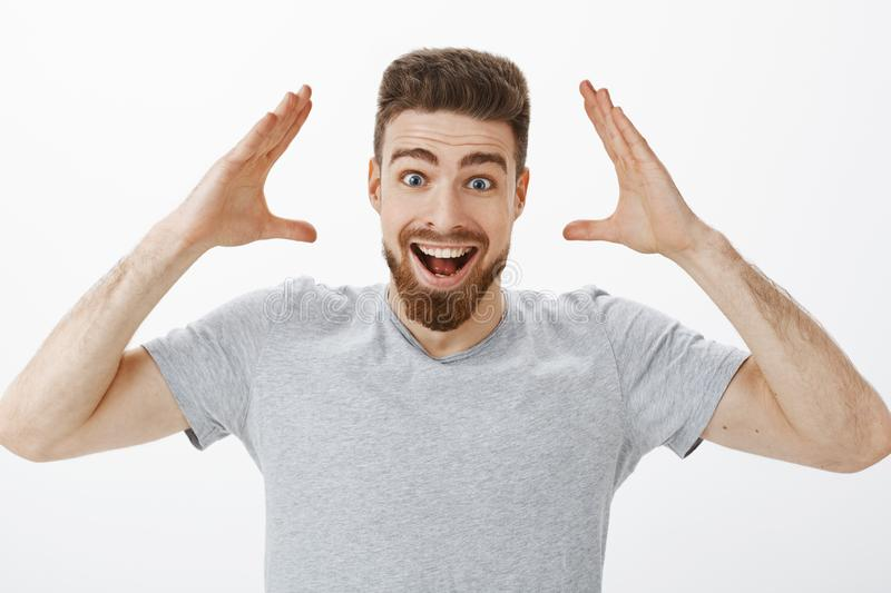Can you imagine I got job. Charismatic joyful and excited handsome male model with beard in grey t-shirt raising hands. Near head smiling broadly receiving good royalty free stock image
