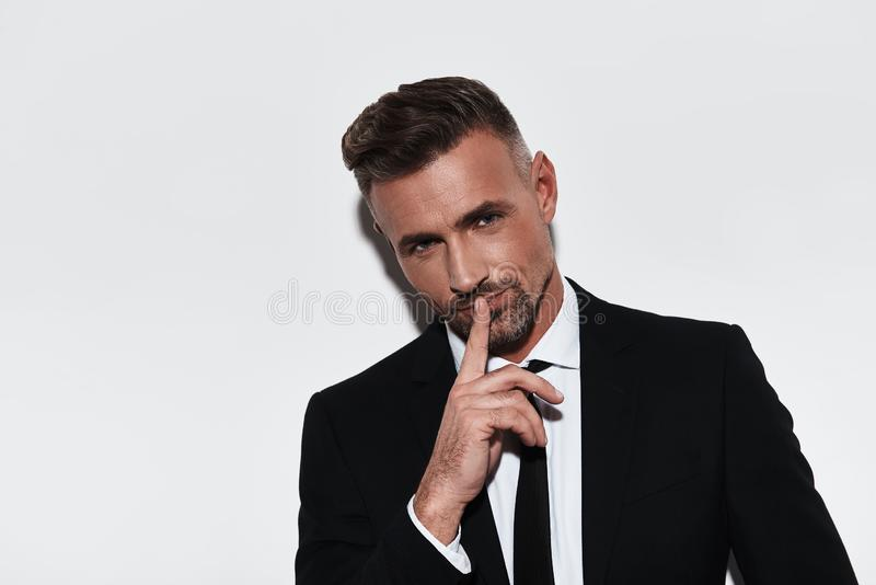 Can you keep a secret?. Handsome young man in full suit keeping index finger by his lips and smiling while standing against white background stock image