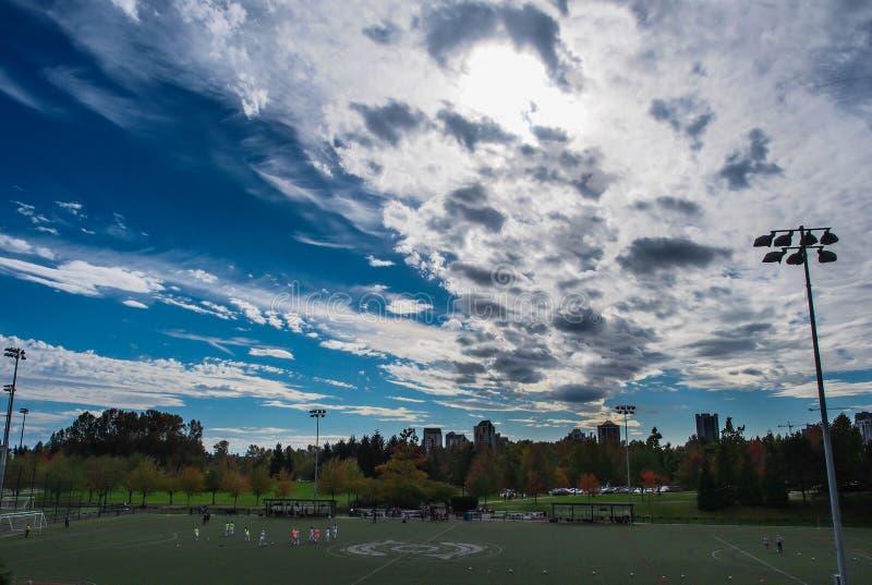 Canadá, Vancôver - o céu nebuloso sobre um campo de futebol com elevação aumenta no fundo imagem de stock royalty free