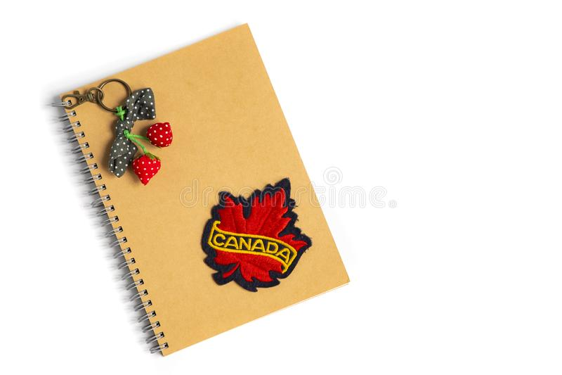A canada badge on a brown notebook. A red maple leaf cloth badge with bright yellow Canada text on a brown notebook. Isolated on white background.  July 14th stock image