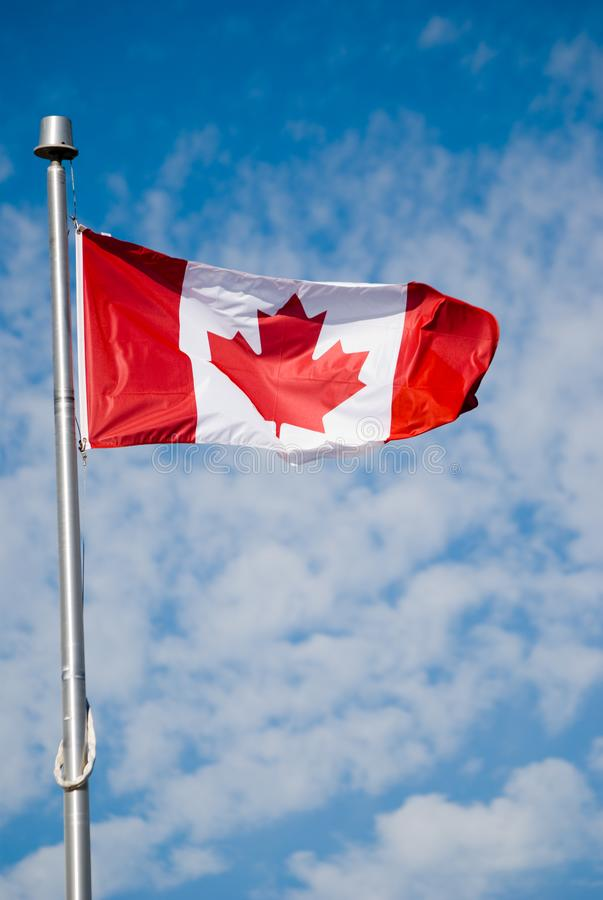 Canada Flag on a Cloudy Day. A Canadian flag against a cloudy sky canada color image vertical travel emblem identity independence symbol patriotic pole day blue stock photography