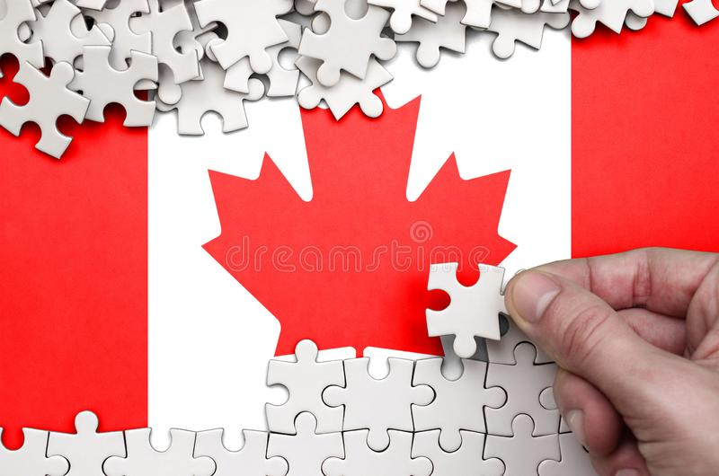 Canada flag is depicted on a table on which the human hand folds a puzzle of white color royalty free stock image