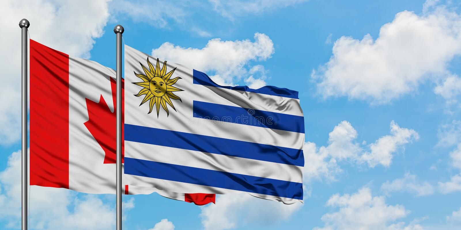 Canada and Uruguay flag waving in the wind against white cloudy blue sky together. Diplomacy concept, international relations. Diplomacy concept, international stock image