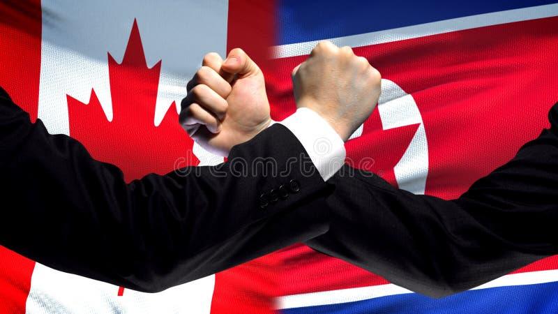 Canada versus de confrontatie van Noord-Korea, vuisten op vlagachtergrond, diplomatie royalty-vrije stock foto