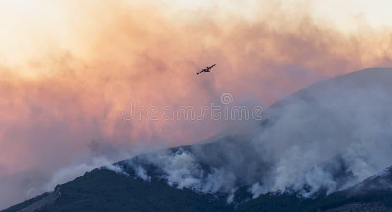 Canadair bezig het uitzetten van een reusachtige brand in het mooie zonsonderganglicht stock fotografie