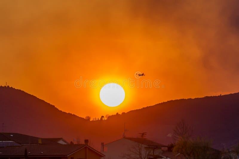Canadair-Propellerflugzeug fliegt über eine Stadt gegen einen schönen Sonnenuntergang stockfotos