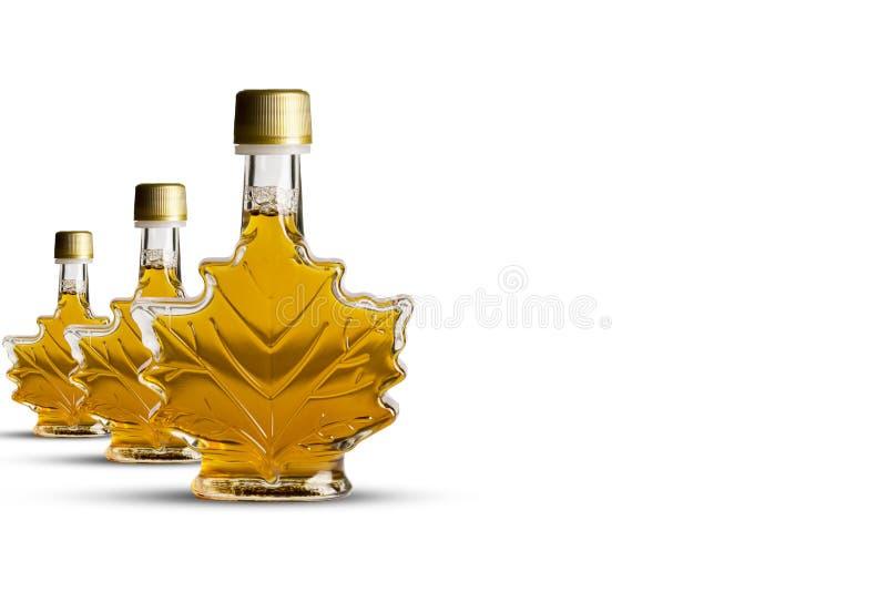 Canadese ahornstroop in drie transparante flessen met bladvorm die op witte achtergrond wordt geïsoleerd royalty-vrije stock foto