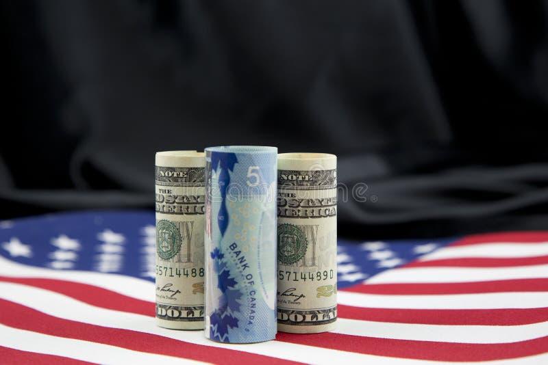 Canadese die dollar tussen Amerikaanse munt wordt vastgeklemd stock afbeeldingen
