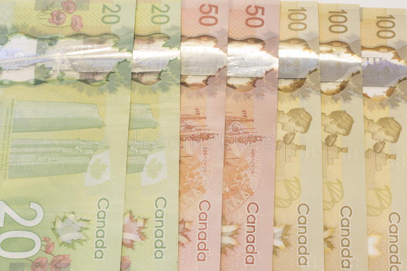 Canadian Bills. Three sets of Canadian dollar bills lined up on a table. They include $20 (Twenty), $50 (Fifty), $100 (One Hundred dollars royalty free stock photo