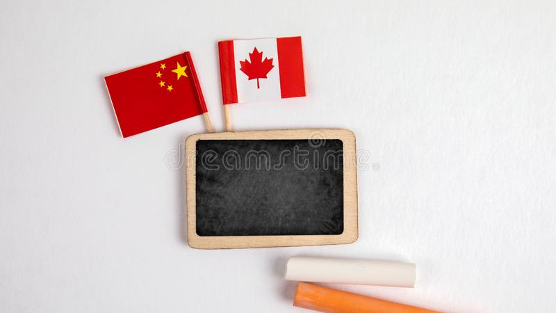 Canadian and Chinese flags. Small whiteboard with chalk. Top view on a white background. Mockup, copy space royalty free stock photos