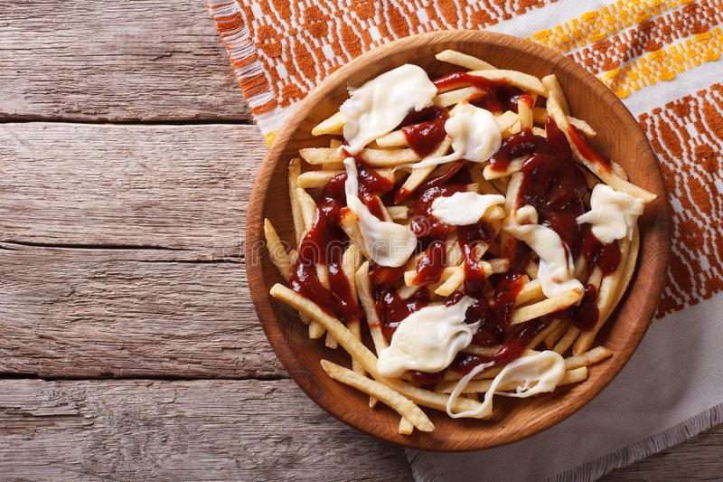 Canadian cuisine: poutine with sauce and cheese. horizontal top royalty free stock photo