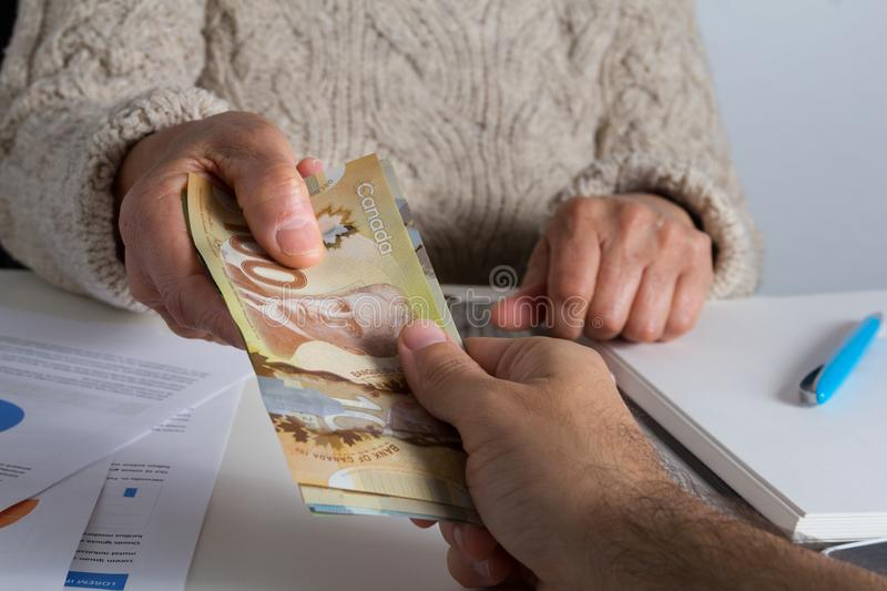 Canadian currency. Dollars. Old person delivering large amount o royalty free stock photography