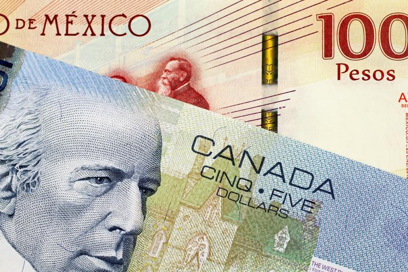 A Canadian 5 Dollar bill with a Mexican 100 peso note. A close up image of a 5 Canadian dollar bill with a 100 Mexican Peso Bank note royalty free stock photos